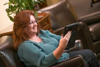 A UMA Student sits in a lounge chair, and accesses her coursework on a tablet.