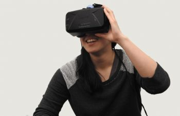 A woman experiencing virtual reality, smiling.