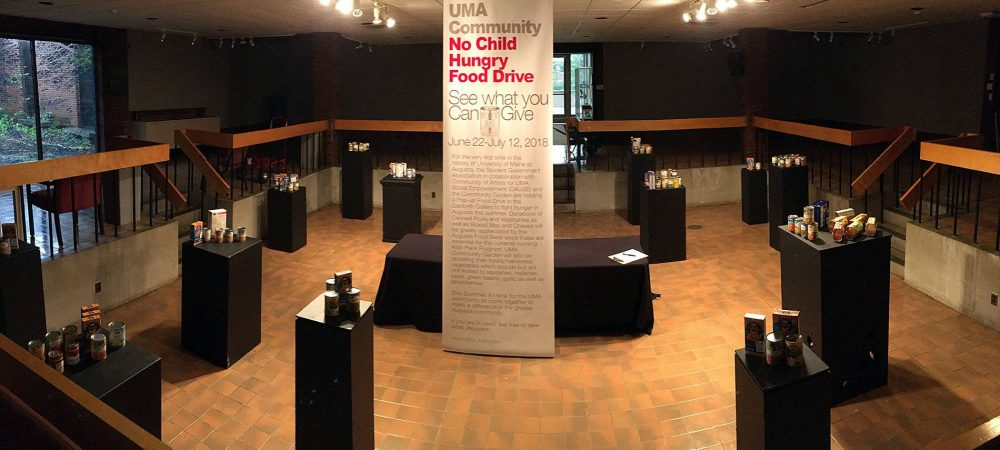 "Cans and boxes of non-perishable food items sit atop display pedestals dispersed throughout the inner section of the gallery, surrounding a large banner that reads ""No Child Hungry."""