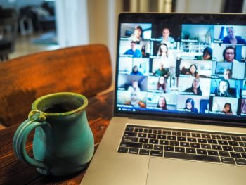A coffee mug next to a laptop. On the screen a Zoom conference is displayed.