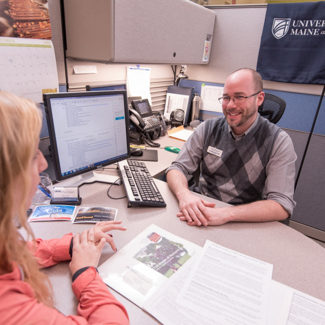 UMA Admissions Counselor working with student