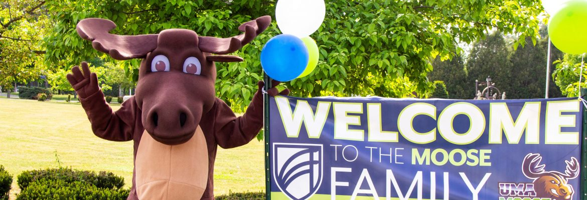 "Augustus the Moose standing next to a banner that reads ""Welcome to the Moose Family."""