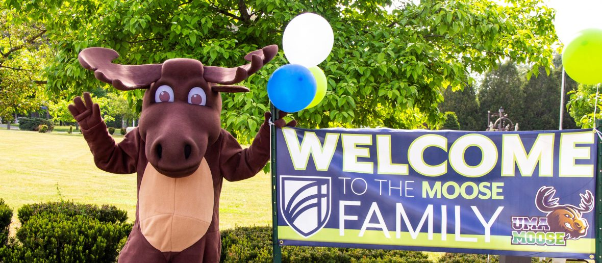 """Augustus the Moose standing next to a banner that reads """"Welcome to the Moose Family."""""""