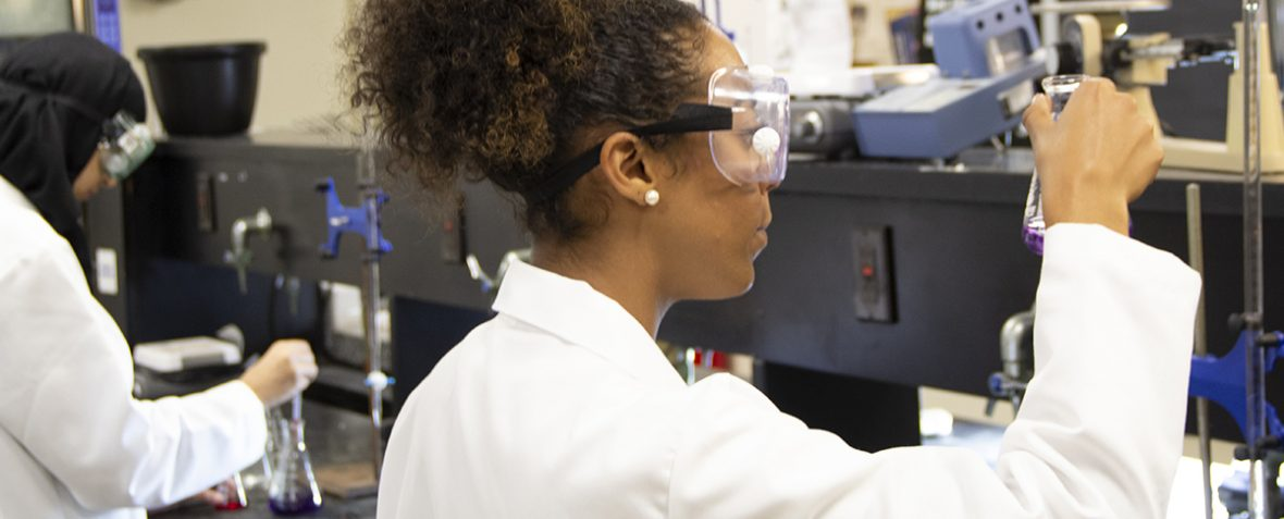 two students in lab coats and googles doing chemistry