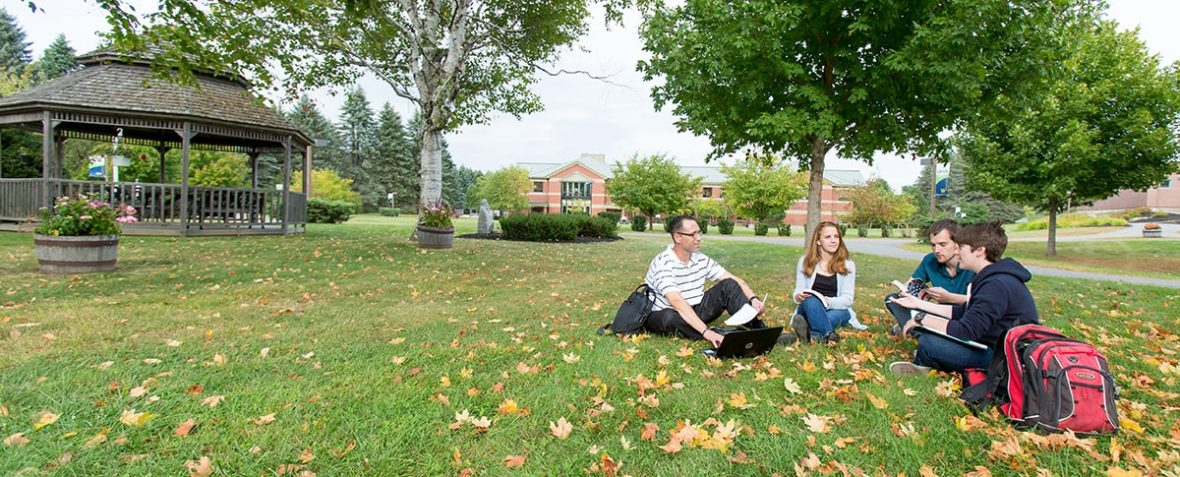Four students sitting on campus lawn.