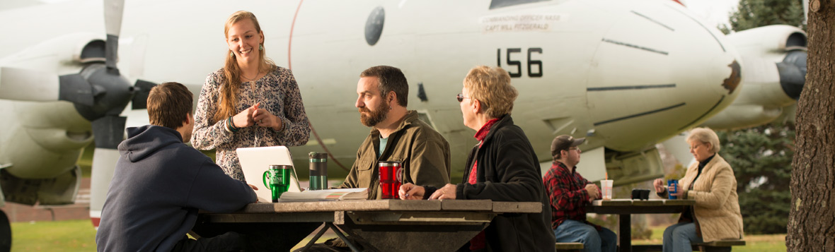 UMA Brunswick Center - students sitting at a picnic table next to the iconic planes on Brunswick Landing