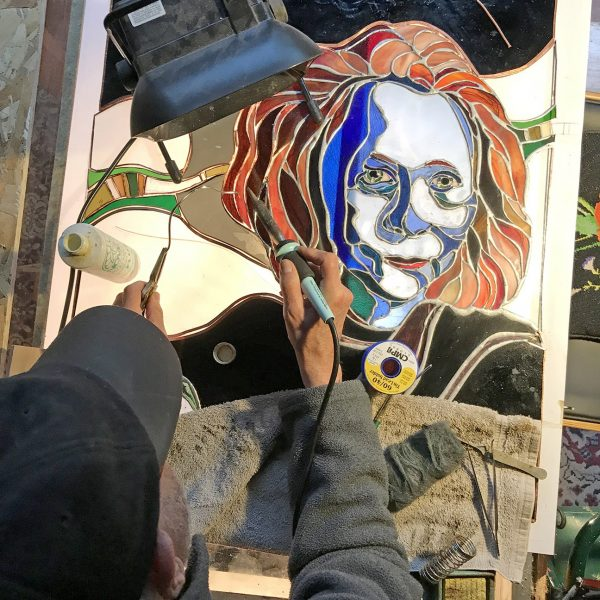 Roger Richmond at work on stained glass portrait of Edna St. Milay.
