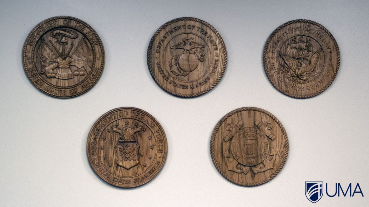 These wooden seals representing the 5 branches of service are displayed in the Veterans Academic Center at UMA.