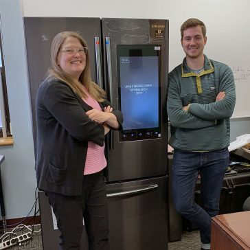 Dr. Betina Tagle on the left and Pierre Laot on the right posing next to the smart fridge associated with the IoT grant