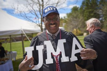 "A U.S. Navy Veteran holdin up white letters that spell ""UMA"""