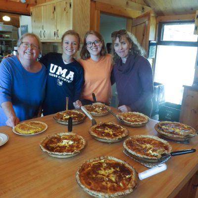Participants posing with a row of pies at the French Immersion weekend.