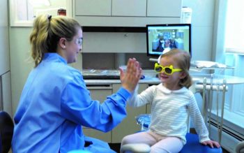 A child giving a high five to a dental student at the Give Kids A Smile Day event.