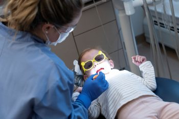 UMA Dental Assisting student cleans the teeth of a child.